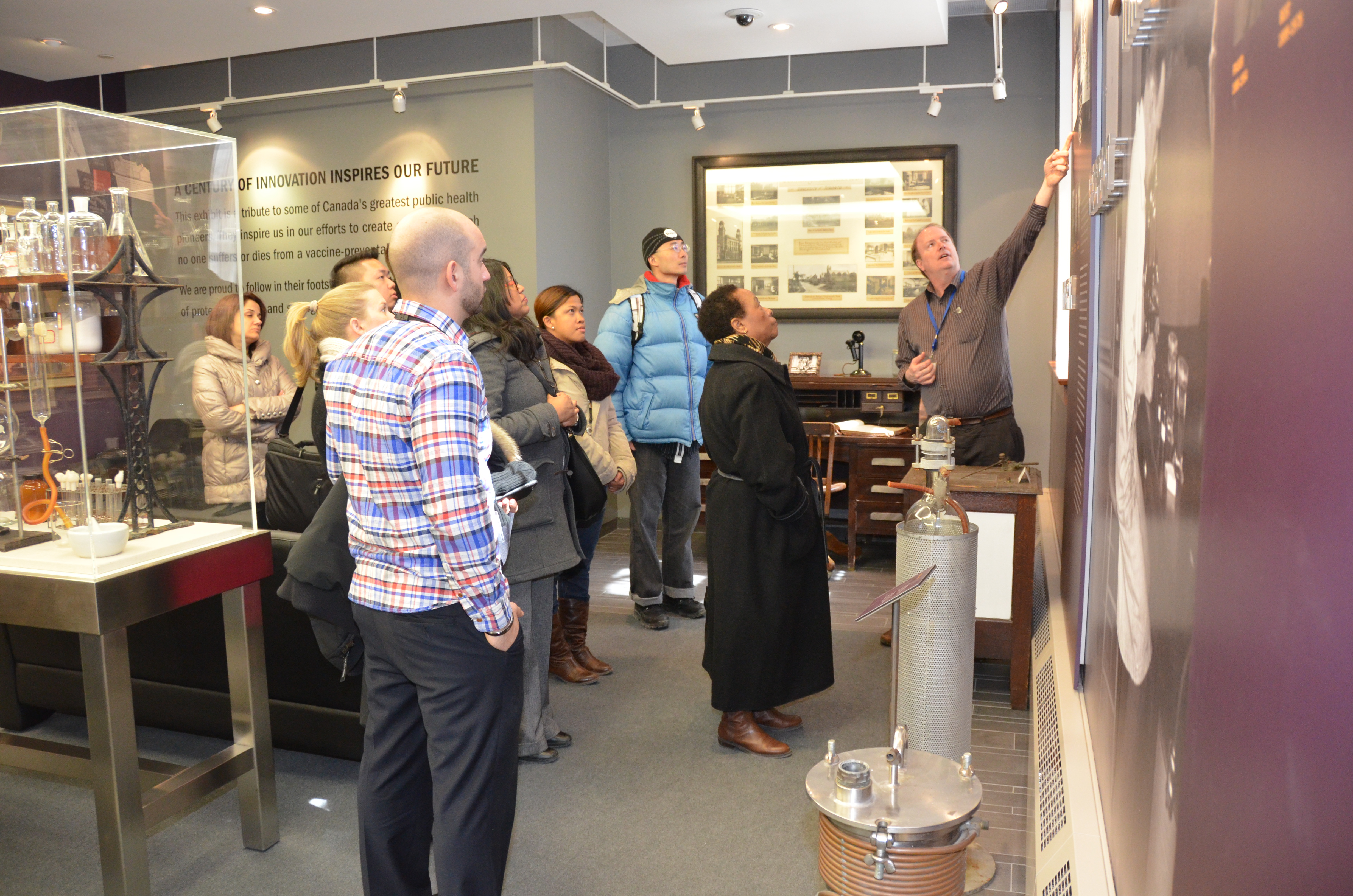 Christopher Rutty leading a group of new employees through one of his regular tours of Sanofi Pasteur Canada's Heritage Room at the Connaught Campus.