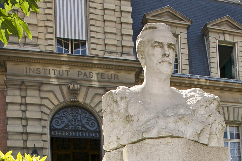Entrance to the Pasteur Institute building in Paris with a statue of Louis Pasteur at the front.