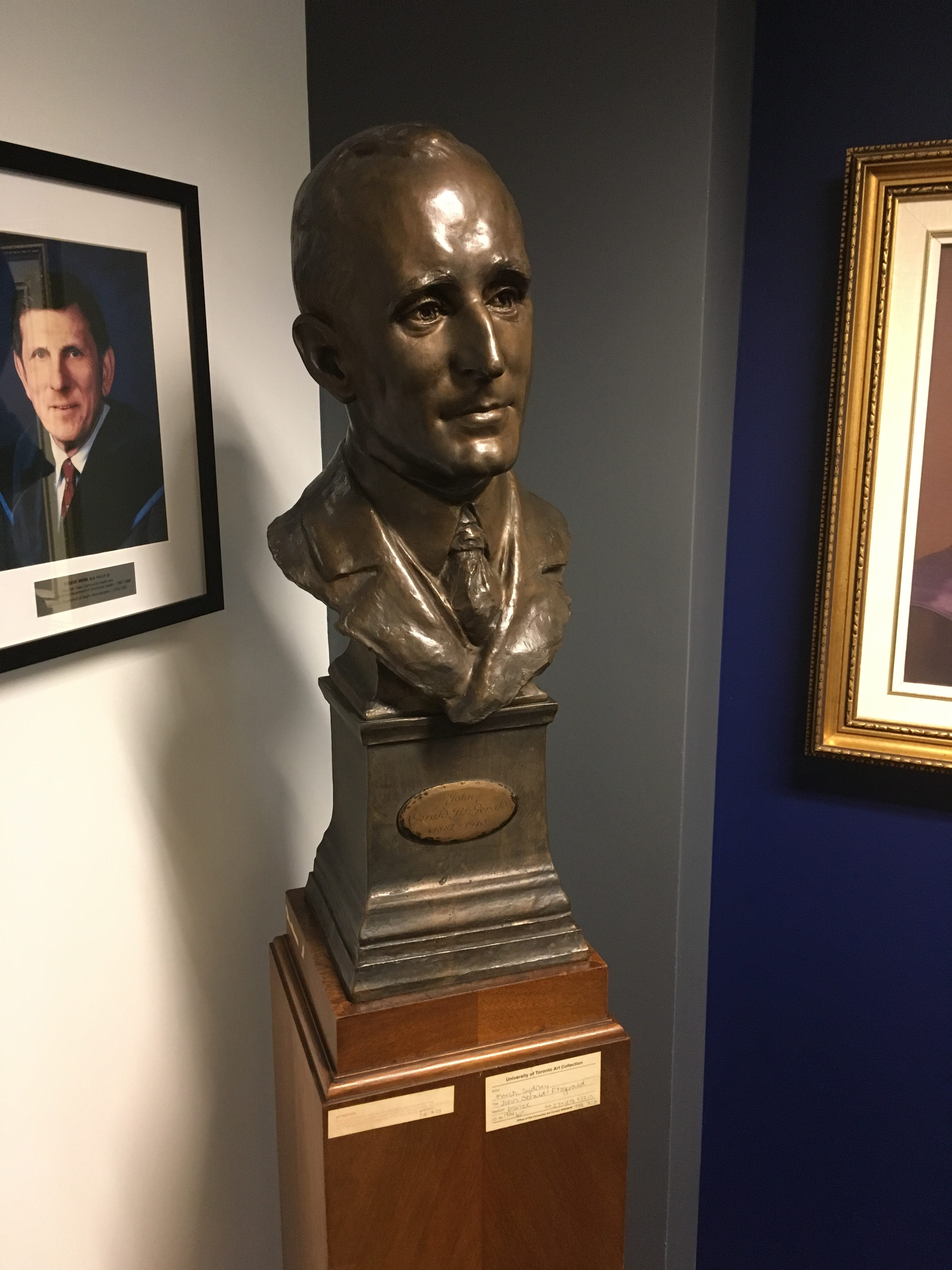 The bronze bust of Dr. John G. FitzGerald in the main 6th floor lobby of the Dalla Lana School of Public Health (DLSPH) has an interesting story. In August 1925, FitzGerald had set sail for Europe with Dr. Frederick Banting, who was bound for Stockholm to receive his Nobel Prize for the discovery of insulin. Somewhere between Labrador and Newfoundland, Banting set up an easel on deck to paint an iceberg when he met British sculptors, Sydney and Vernon March, famous for their bronze bust portraits. During the trip, FitzGerald commissioned Sydney March to create a bronze bust of himself for the library of the new School of Hygiene building. The bust was completed for the opening of the Hygiene Building in June 1927, and remained there until it was moved across the street to the DLSPH lobby 91 years later.  On his death in June 1940, FitzGerald's ashes were placed inside the bust, but on the death of his wife, Edna, in 1958, his ashes were then interred together with hers at Mt. Pleasant Cemetery.