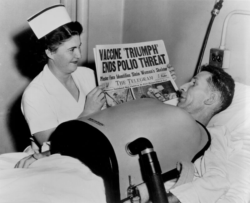 This dramatic photo captures the widely celebrated news of the success of the polio vaccine field trial, juxtaposed with a man recovering from polio in a portable respirator and for whom the vaccine came too late