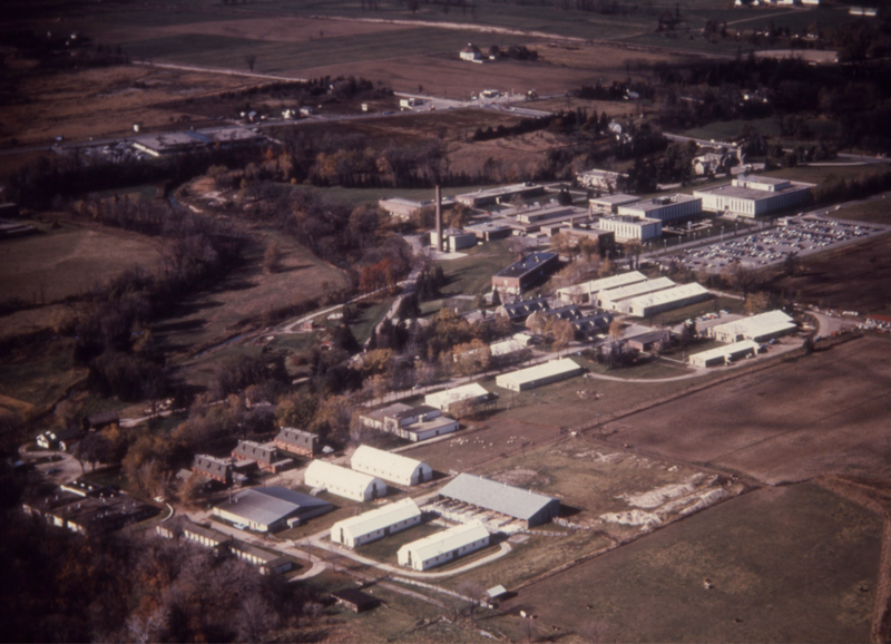 Aerial view of Connaught Laboratories' Dufferin Division, looking at the site from the south-east to the north-west, with the corner of Steeles Ave. West and Dufferin Street at the top left. The photo was taken sometime in early 1971, prior to the start of construction of Building 90, which would be built in the space to the right of the three long white buildings and next the similar white building furthest to the right of the photo.